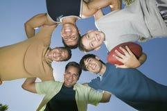 Мальчик (13-15) держа футбол с братьями и отцом в взгляде груды снизу. Стоковые Фото
