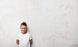 Мальчик держит его заднюю часть и усмехаться рук позади Стоковое Фото