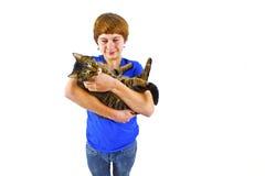 Мальчик держит его кота tabby в его оружиях стоковая фотография