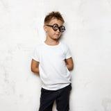 Мальчик держит его руки позади подпирает и взгляды Стоковые Фотографии RF