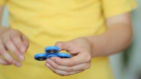 Мальчик держит популярный обтекатель втулки непоседы игрушки в руках Сброс стресса Анти- непоседы стресса и релаксации, обтекател акции видеоматериалы