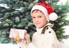 Мальчик держит подарок на рождество в белой коробке Стоковые Изображения RF