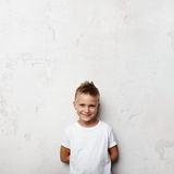 Мальчик держит руки позади задний и усмехающся дальше Стоковые Фото