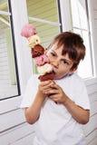 Мальчик есть высокорослый конус мороженого Стоковые Фотографии RF