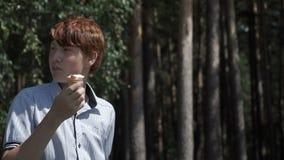 Мальчик есть мороженое в древесинах сток-видео