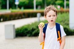 Мальчик есть яблоко на дороге к школе Стоковое Изображение RF