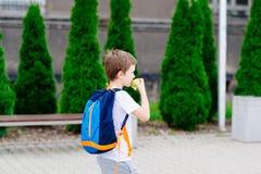 Мальчик есть яблоко на дороге к школе Стоковые Фотографии RF
