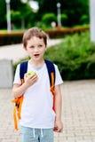 Мальчик есть яблоко на дороге к школе Стоковое фото RF