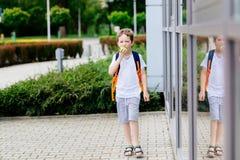 Мальчик есть яблоко на дороге к школе Стоковые Изображения
