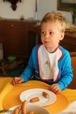 Мальчик есть frankfurters от белой плиты Стоковое Изображение