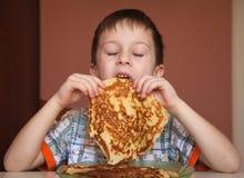 Мальчик ест блинчики стоковая фотография
