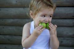 Мальчик ест зеленые яблока Стоковые Фотографии RF