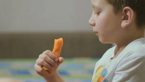 Мальчик ест морковь дома видеоматериал