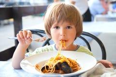 Мальчик ест спагетти Стоковые Изображения
