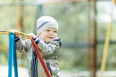 Мальчик ехать качание в спортивной площадке парка Стоковые Фотографии RF