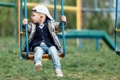 Мальчик ехать качание в спортивной площадке парка Стоковые Изображения RF