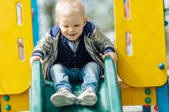 Мальчик ехать качание в спортивной площадке парка Стоковая Фотография