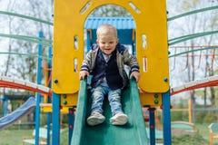 Мальчик ехать качание в спортивной площадке парка Стоковая Фотография RF
