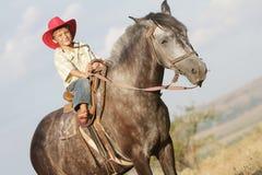 Мальчик ехать лошадь на ферме outdoors Стоковое Изображение RF