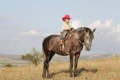 Мальчик ехать лошадь на ферме outdoors Стоковое Фото
