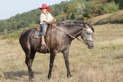 Мальчик ехать лошадь на ферме outdoors Стоковая Фотография RF