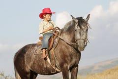 Мальчик ехать лошадь на ферме outdoors Стоковое фото RF