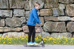 Мальчик ехать самокат Стоковые Фотографии RF