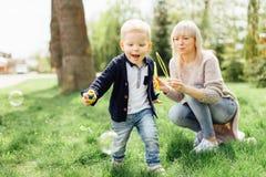 Мальчик делает пузыри с его матерью на парке Стоковое фото RF
