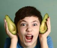 Мальчик делает уши эльфа от halfs авокадоа Стоковая Фотография