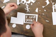 Мальчик делает origami - автомобиль и семья, дети, родитель, я тебя люблю текст, взгляд сверху на деревянной предпосылке Стоковое фото RF