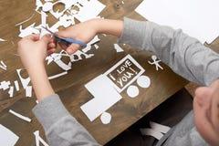 Мальчик делает origami - автомобиль и семья, дети, родитель, я тебя люблю текст, взгляд сверху на деревянной предпосылке Стоковые Фото