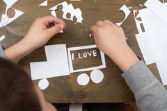 Мальчик делает origami - автомобиль и семья, дети, родитель, я тебя люблю текст, взгляд сверху на деревянной предпосылке Стоковые Изображения RF