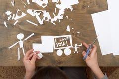 Мальчик делает origami - автомобиль и семья, дети, родитель, я тебя люблю текст, взгляд сверху на деревянной предпосылке Стоковые Фотографии RF