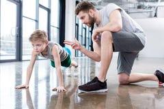 Мальчик делать нажимает поднимает с тренером Стоковые Фотографии RF