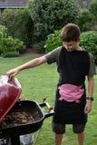 Мальчик делая барбекю Стоковые Фотографии RF