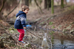 Мальчик, делая большой выплеск на пруде Стоковое фото RF