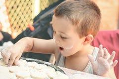Мальчик делая вареники на таблице Стоковое Изображение