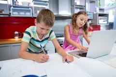 Мальчик делая его домашнюю работу пока девушка используя компьтер-книжку в кухне Стоковые Фото