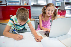 Мальчик делая его домашнюю работу пока девушка используя компьтер-книжку в кухне Стоковое Фото