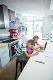 Мальчик делая его домашнюю работу пока девушка используя компьтер-книжку в кухне Стоковые Изображения