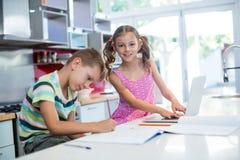 Мальчик делая его домашнюю работу пока девушка используя компьтер-книжку в кухне Стоковое Изображение