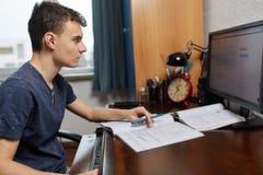 Мальчик делая домашнюю работу на его компьютере Стоковое Изображение