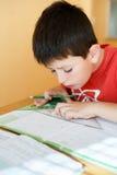Мальчик делая домашнюю работу школы Стоковая Фотография