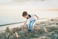 Мальчик делая sandcastle на пляже стоковое фото rf