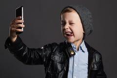 Мальчик делая selfie стильный ребенок в кожаных пальто и шляпе Ягнит эмоция Стоковое фото RF