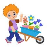 Мальчик засаживая цветки и работая в саде Стоковое фото RF