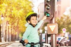 Мальчик задействуя на его велосипеде и уча правила движения Стоковое Фото