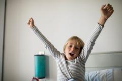 Мальчик зевая на кровати в спальне дома Стоковые Фотографии RF