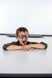 Мальчик зевая пока сидящ на таблице в классе Стоковые Изображения RF
