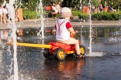 Мальчик играет в фонтане города на жаркой погоде Стоковые Изображения RF